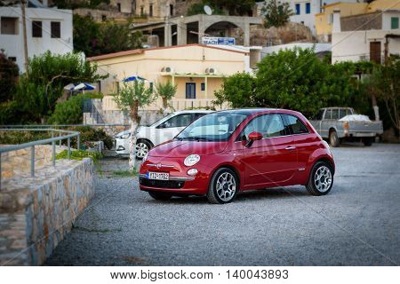 CHORA SFAKION, CRETE, GREECE - JULY 2016: Red Fiat 500 stays parked at street of Chora Sfakion town on Crete island