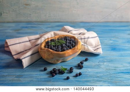 Wooden bowl full with blueberry on vintage blue wooden table