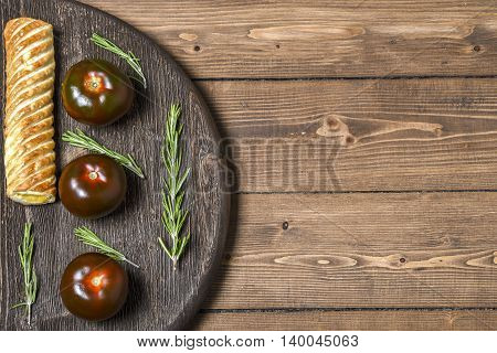 Black tomato with pie on a wooden Board, place for text