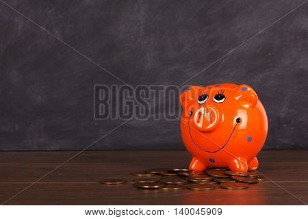 Coins And Orange Piggy Bank On A Wooden Surface