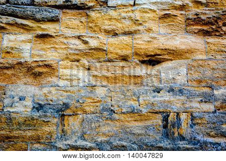 Old wall from a rough yellow limestone