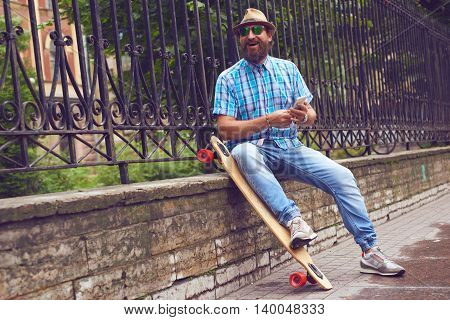 Hipster man sitting at the park with long board. Handsome men in sunglasses and hat posing outdoor. Tonning image