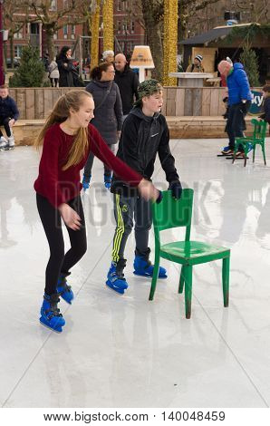 AMSTERDAM NETHERLANDS - DECEMBER 26 2015: Two unknown teenagers skating with the help of a chair in amsterdam