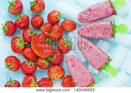 Homemade strawberry yogurt popsicles refreshing summer food background top view