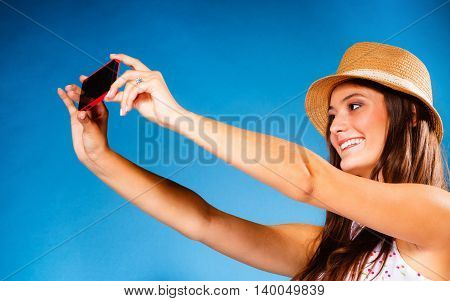 Technology internet and happy people concept - teen girl taking self picture selfie with smartphone camera woman using cell phone on blue