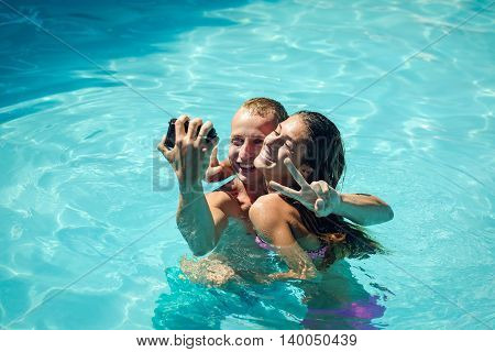 young happy sexy couple of pretty woman in swimsuit and muscular smiling man taking photo with camera in blue water of swimming pool at sunny summer vacation