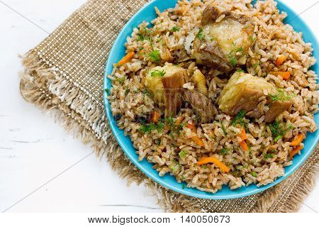 Traditional Uzbek pilaf of devzira rice and lamb blank space for text on blue background