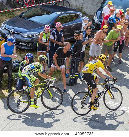 Col du Glandon France - July 23 2015: Chris Froome in Yellow Jersey followed by Rafal Majka of Thinkoff-Saxo Team riding in a beautiful curve at Col du Glandon in Alps during the stage 18 of Le Tour de France 2015.