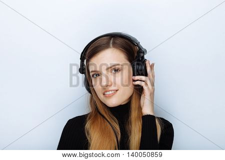 Portrait Of Happy Smiling Young Beautiful Woman In Black Sweater Big Dj Headphones Posing Against Wh