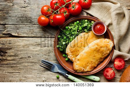 Chicken schnitzel with cheese or cordon bleu with green salad and cherry tomatoes in a rustic style on the old wooden background top view blank space for text