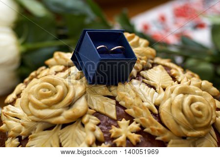 Wedding rings in a blue gift box on wedding pan loaf. Blurred background