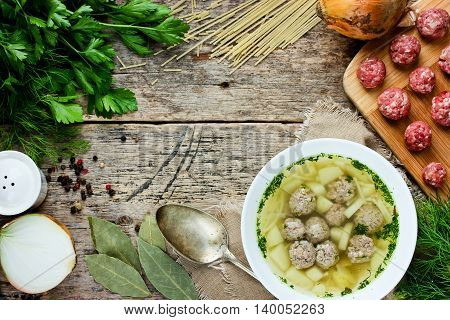Meatball soup with noodles potato and greens on wooden table with ingredients top view blank space for text