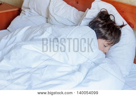young child boy sleeping in bed at home, indoor portrait