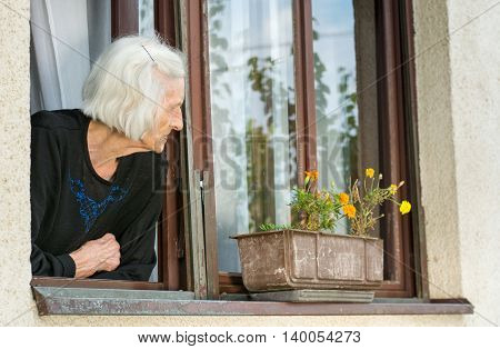 Senior Woman Alone On House Window