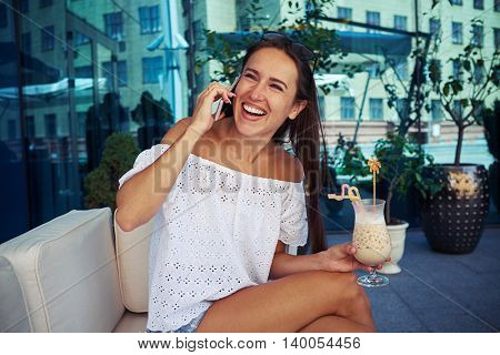 Young beautiful dark-haired female is enjoying her cocktail on open terrace of modern business center and chatting on the phone