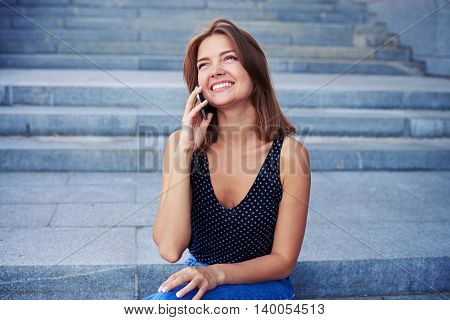 Young beautiful woman in casual clothes is sitting on street stairs and talking on the phone with happy expression on her face