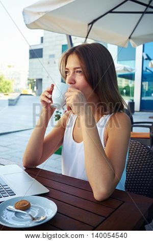 Close-up of beautiful female drinking coffee with thoughtful look in open air cafe near business center