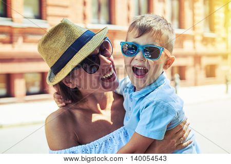 Small boy in sunglasses is laughing happily in his mother's arms during their walk in the city on warm sunny summer day
