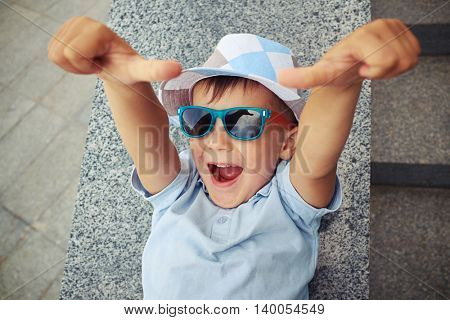 Joyful small boy in sunglasses is giving two thumbs up while lying on street stairs parapet on summer day