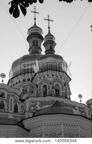 Golden tops and crosses of Christian Orthodox Abbey. Vertical black&white photo