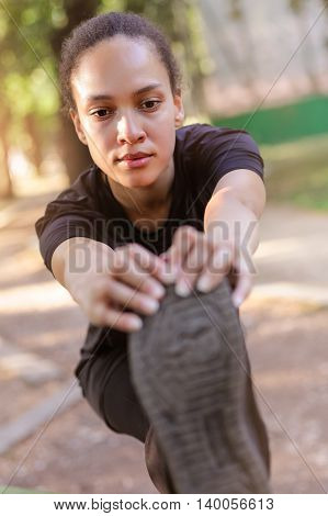 Training Outdoors. Fit Young Woman Stretching Her Legs.