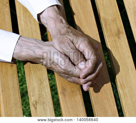 The palms of wrinkled hands of an elderly man