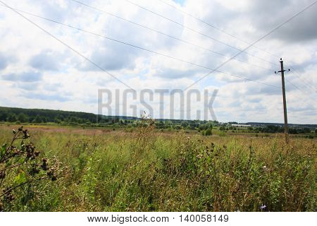 Summer field wire and electric pole in the summer.