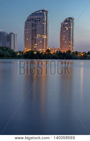 Night city buildings reflected in river water. HDR