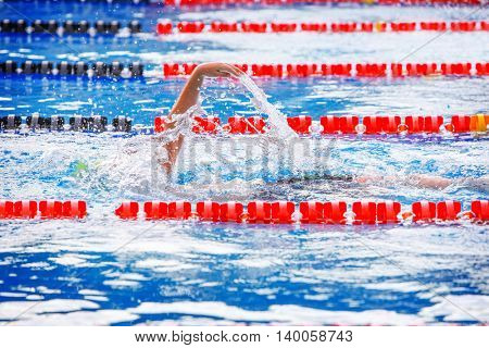 Backstroke swimmer with splash, motion blur on swimmer, focus on splash.  Pool colors red white and blue.