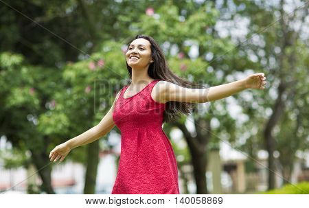 Free Happy young Woman Enjoying Nature. Beauty Girl Outdoor. Freedom concept. Beauty Girl over garden and Sun. Enjoyment.