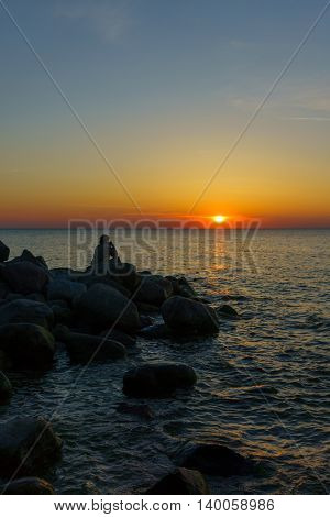 Man sitting on the stones at the seashore and watching beautiful sunset