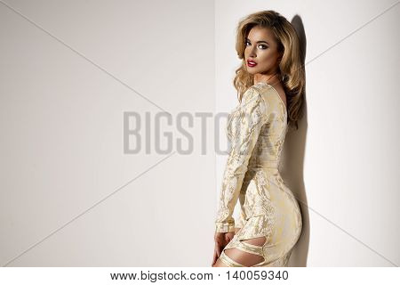 Sexy Blond Lady In Gold Dress On Dark Background
