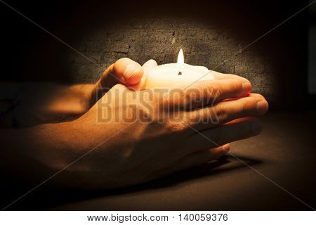 Praying Hands with candle in black old background