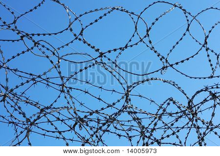 Barbed wire over blue sky