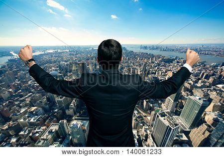 Happy businessman raising his arms in front of a big city