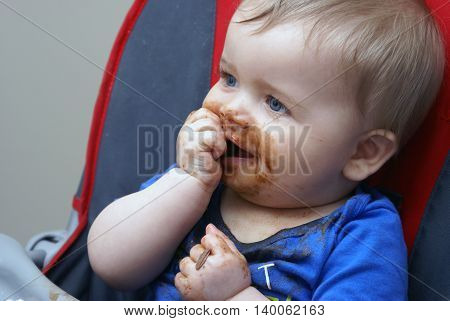 A baby boy experiences his first piece of chocolate.