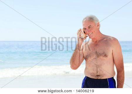 Senior Man Listening To His Shell