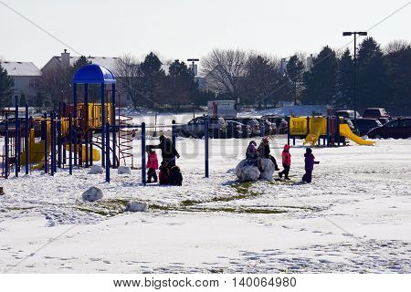 JOLIET, ILLINOIS / UNITED STATES - NOVEMBER 24, 2015: Children play in the snow, in the playground behind the Wesmere Elementary School, after a November snowstorm in Joliet.