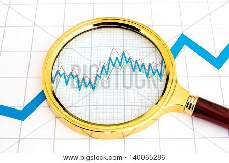 Magnifier a successful businessman is on report and shows details of trend graph, helping analysis of situation with investment income. Concept of business intelligence