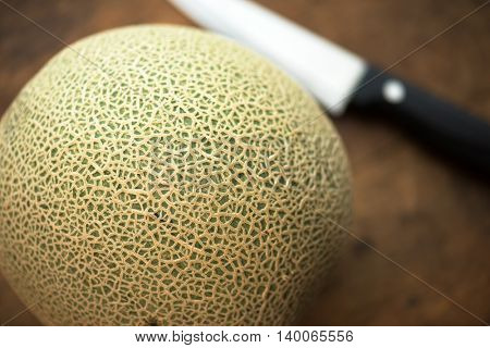 Melon on a rustic kitchen table, with knife in background. Intentionally shot with extremely shallow depth of field.