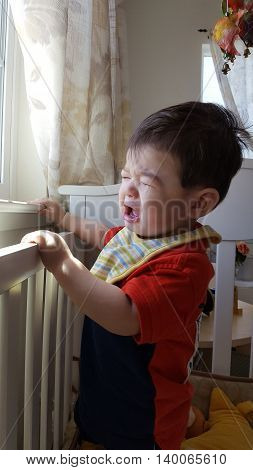 Adorable Crying baby boy next the window