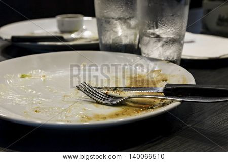 Empty white plate after dinner with glass of water