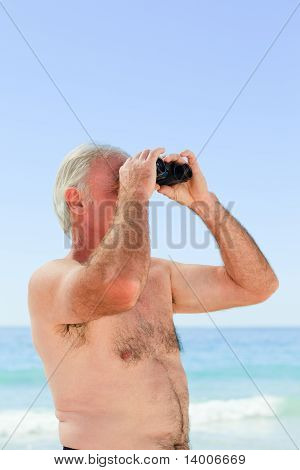 Senior Man Bird Watching At The Beach