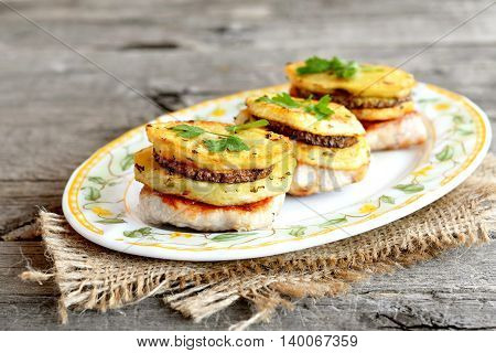 Fried Turkey fillet with potatoes, zucchini and parsley on a plate and on a burlap. Meat with vegetables on a wooden table. Delicious lunch or dinner recipe. Closeup