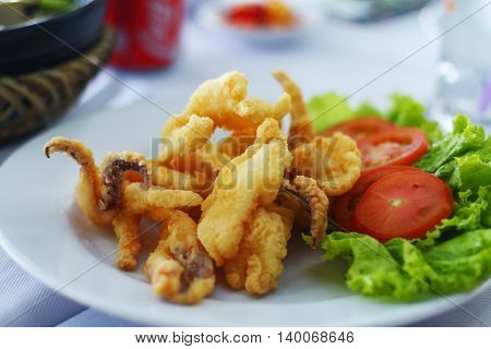 Yummy look squid tempura (batter fried) in white plate with vegetable