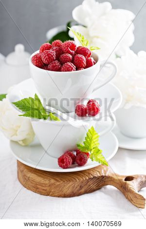 Fresh raspberries in white stacked cups with flowers in background