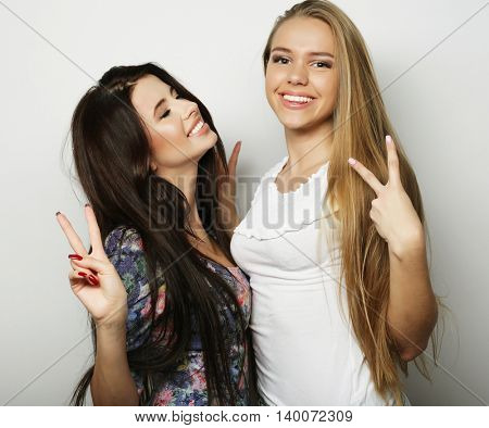 Two young girl friends standing together and having fun. Looking