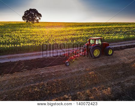 Farmer in tractor preparing land with seedbed cultivator aerial view
