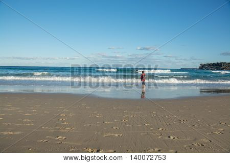 Young person staring at the waves on the beach