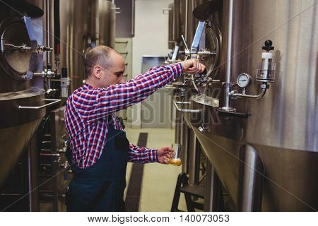 Side view of manufacturer pouring beer in glass from machine at brewery